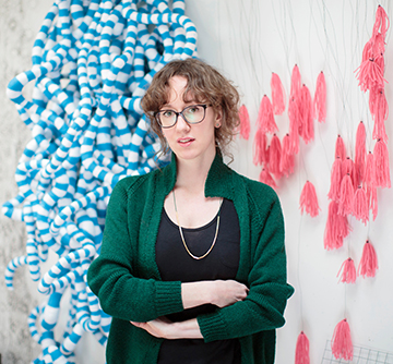 A photograph of artist Anna Ray standing  in front of fabric pink sculpture
