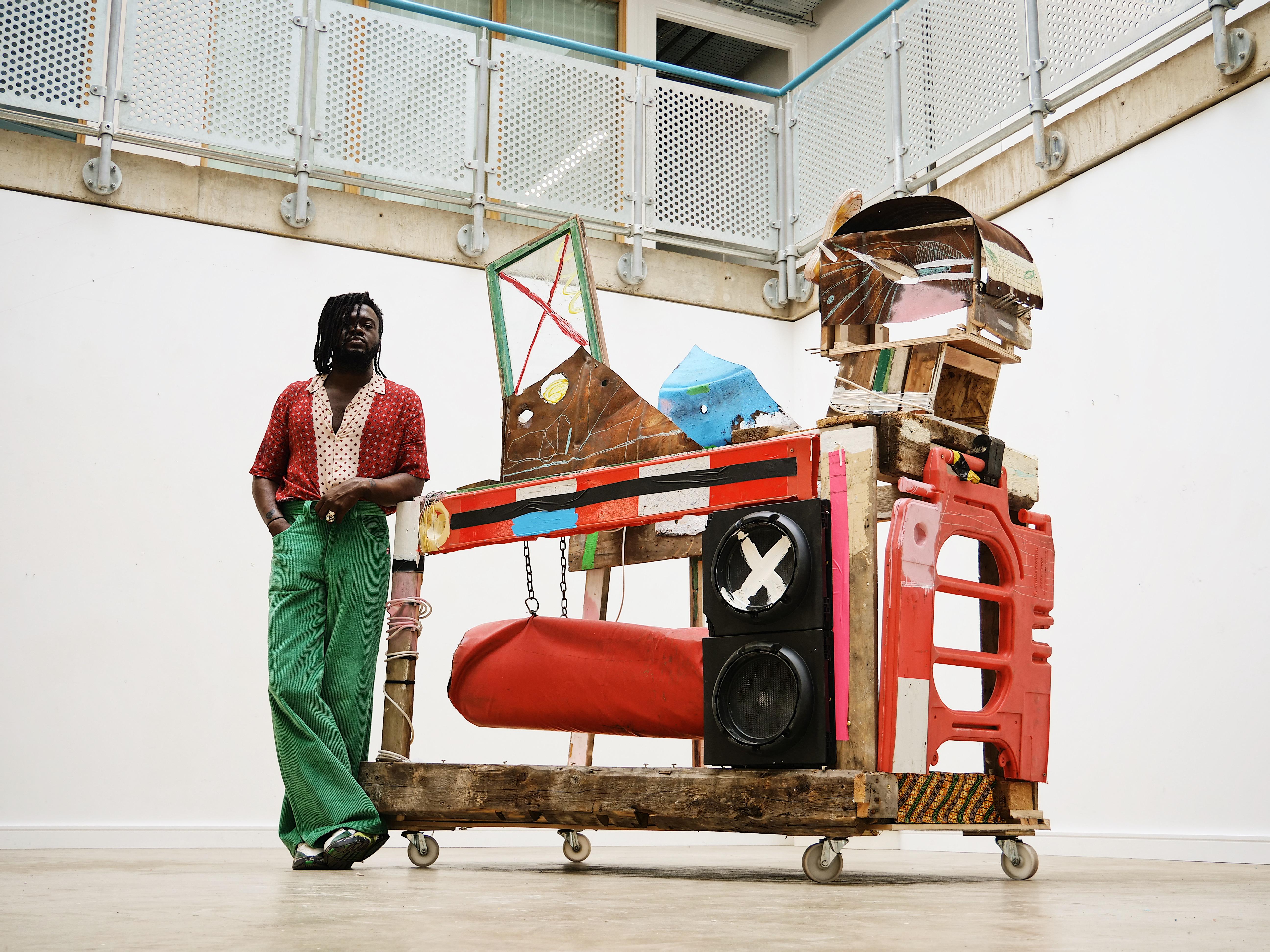 Adebayo Bolaji standing next to his artwork: Trojan,  a horse like structure