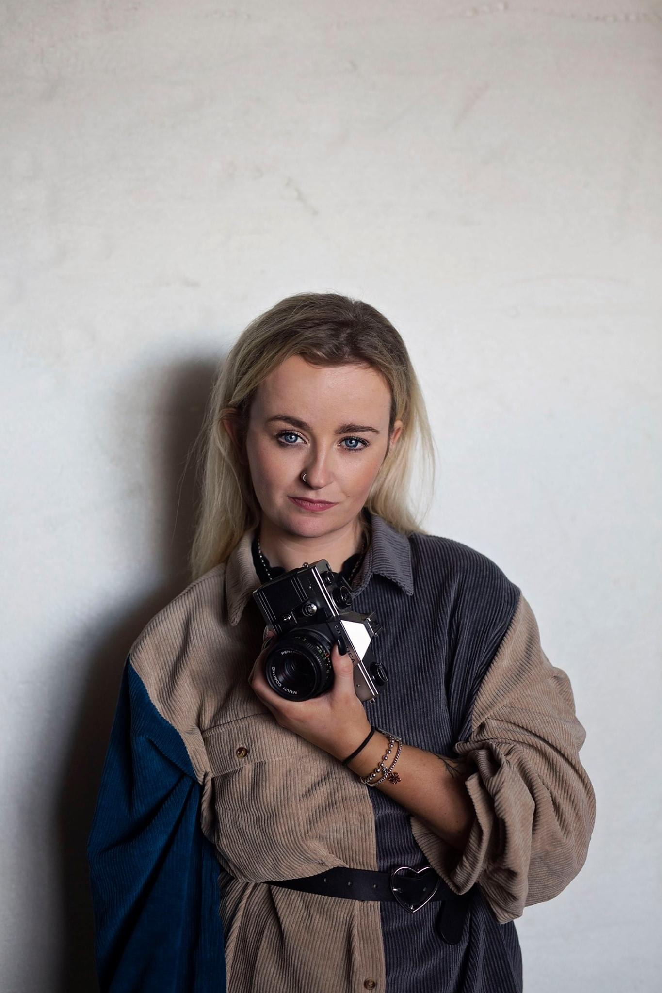 A phtograph of Katie wearing a coat with a camera in hand