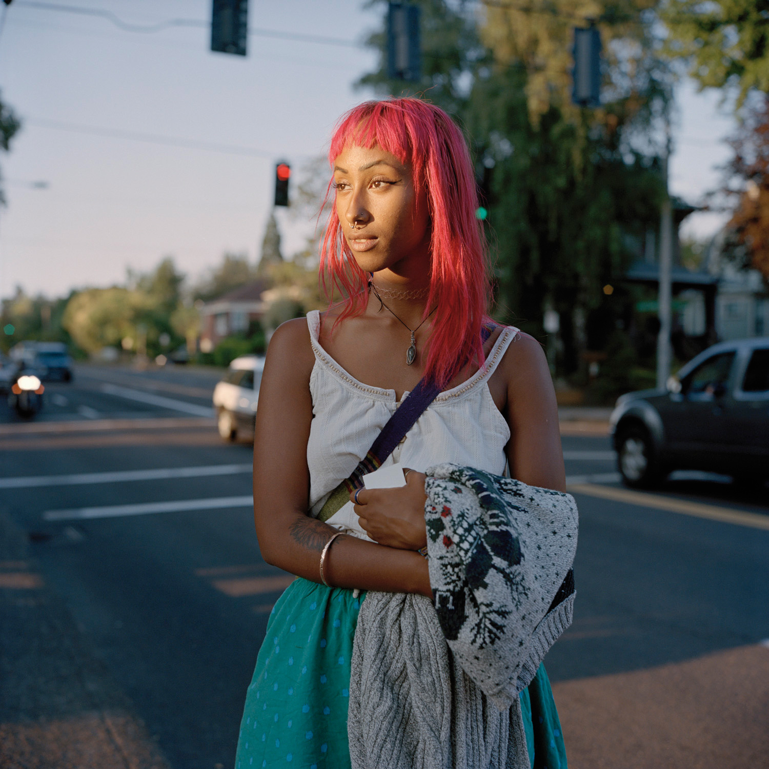 women with bright pink hair, carrying a cardigan starin off to the left. Behind her is a traffic stop light