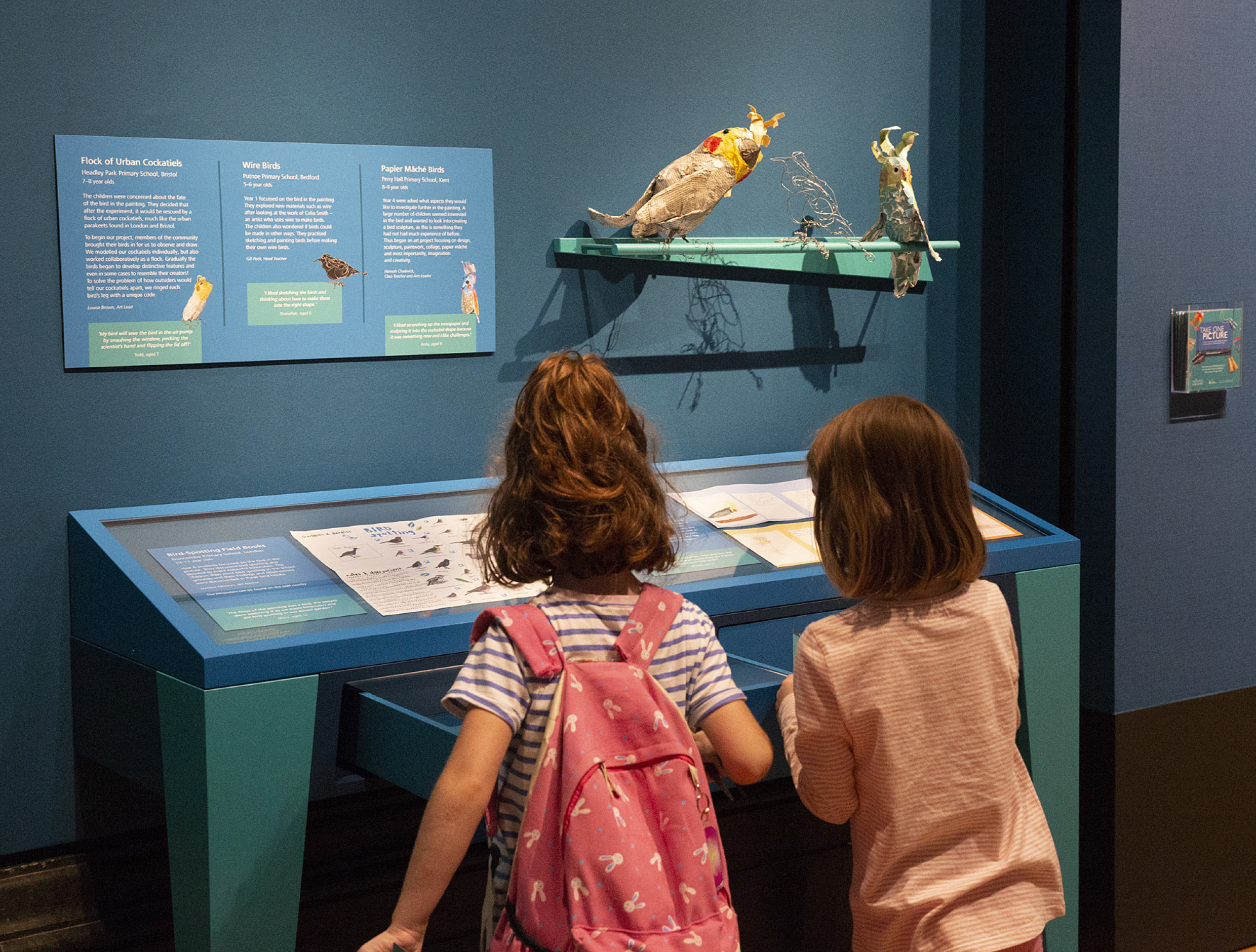 Two small children interacting with exhibition display on birds