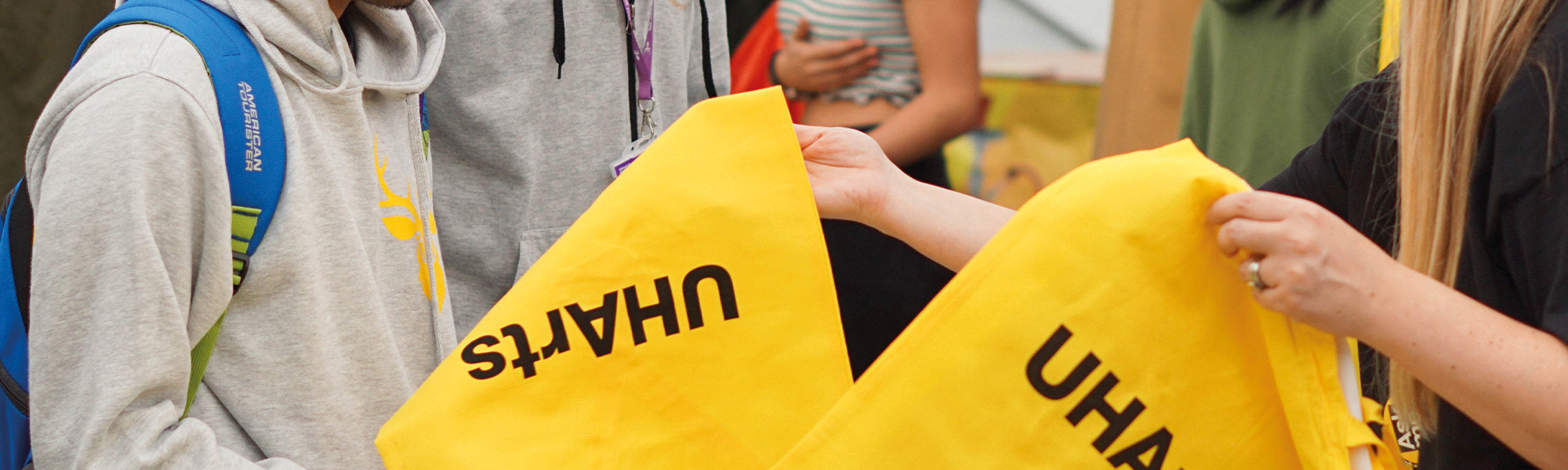 Students handing out yellow UHArts tote bags