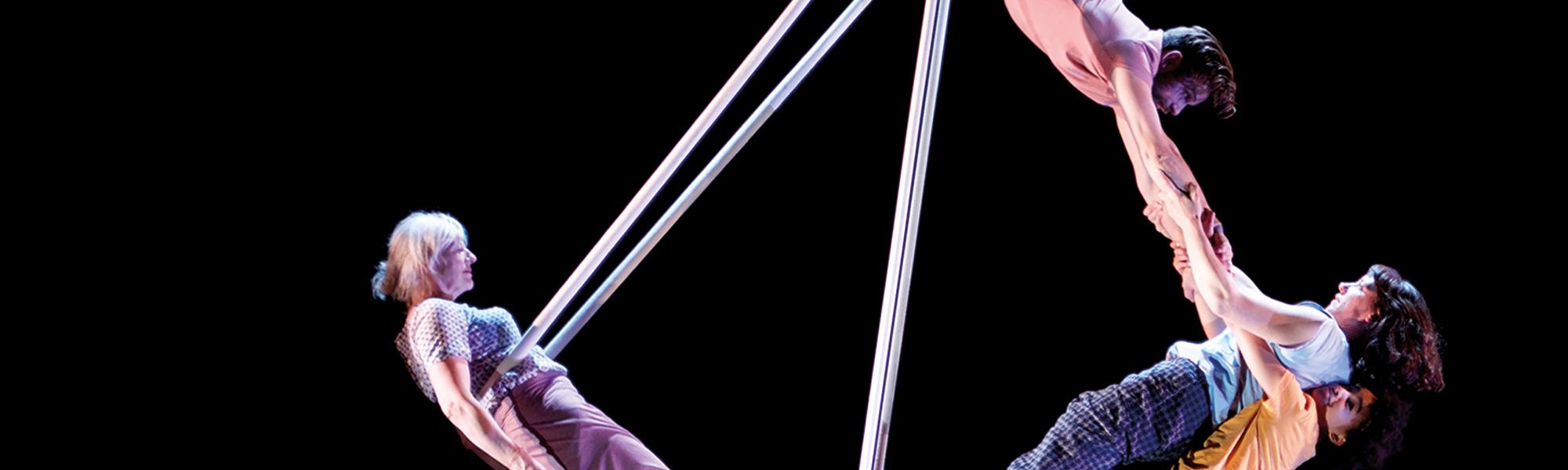 Ockham's Razor performers swinging from trapeze behind black background